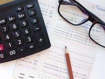 Lápiz, calculadora, lentes y libreta de banco del cuenta de ahorros o estado financiero sobre el fondo blanco Foto de archivo