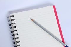 Lápiz con el cuaderno rojo en la tabla blanca Foto de archivo