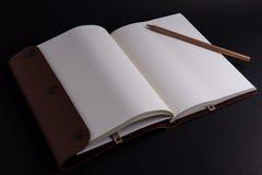 Lápiz con el libro en fondo negro Fotografía de archivo libre de regalías