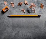 Lápiz de madera de la textura con la afiladura de virutas en fondo oscuro Imagen de archivo libre de regalías
