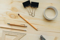 Lápiz de madera, pluma, triángulo, clips más briefpapier, hefter en el escritorio en luz del día Tabla de la oficina Imagen de archivo