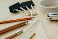 Lápiz de madera, pluma, triángulo, clips más briefpapier, hefter en el escritorio en luz del día Tabla de la oficina Foto de archivo