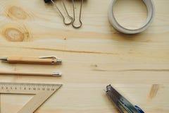 Lápiz de madera, pluma, triángulo, clips más briefpapier, hefter en el escritorio en luz del día Tabla de la oficina Fotos de archivo libres de regalías