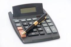 Lápiz de oro y una calculadora en un fondo blanco Imagen de archivo libre de regalías