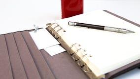 Lápiz del diario de la página en blanco y taza de café roja Fotos de archivo libres de regalías