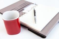 Lápiz del diario de la paginación en blanco y taza de café roja Imagen de archivo