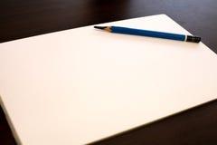 Lápiz del dibujo y Libro Blanco en fondo del marrón oscuro Imagenes de archivo