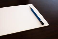Lápiz del dibujo y Libro Blanco en fondo del marrón oscuro Imagen de archivo