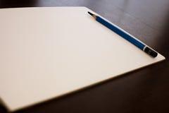 Lápiz del dibujo y Libro Blanco en fondo del marrón oscuro Fotos de archivo libres de regalías