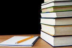 Lápiz en el cuaderno cerca de la pila de libros Fotos de archivo