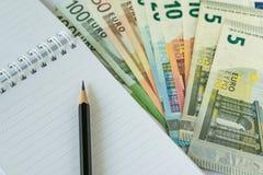 Lápiz en la nota de papel con la pila de billetes de banco euro como economi euro fotografía de archivo