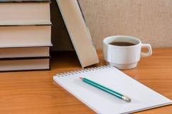 Lápiz en un cuaderno, libros y una taza de té en la tabla fotografía de archivo