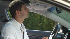 Lápiz labial de la limpieza del hombre de negocios de la mejilla en coche almacen de metraje de vídeo