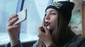 Lápiz labial de la muchacha que mira el teléfono almacen de metraje de vídeo