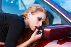 Lápiz labial que pone rubio en usar el espejo de coche Foto de archivo libre de regalías