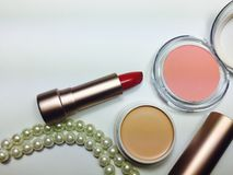 Lápiz labial rojo de la crema hidratante en paquete del oro de la perla Foto de archivo libre de regalías