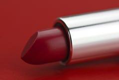 Lápiz labial rojo en fondo rojo Imagen de archivo libre de regalías