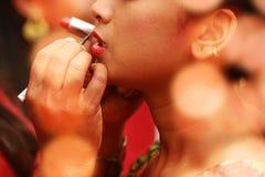 Lápiz labial rojo Primer de la cara de la mujer con Matte Lipstick On Lips rojo brillante Cosméticos de la belleza, concepto del  Foto de archivo libre de regalías