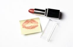 Lápiz labial rojo y nota amarilla de la etiqueta engomada con beso Imagen de archivo libre de regalías