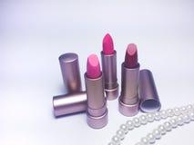 Lápiz labial rojo y rosado de la crema hidratante en paquete del oro de la perla Fotos de archivo