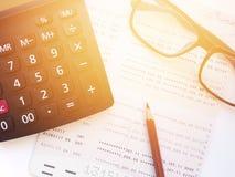 Lápiz, lentes, libreta de banco de la calculadora y del cuenta de ahorros o estado financiero sobre el fondo blanco Imagenes de archivo