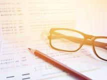 Lápiz, lentes y libreta de banco del cuenta de ahorros o estado financiero sobre el fondo blanco Imagenes de archivo