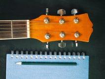Lápiz, libro y guitarra fotografía de archivo libre de regalías