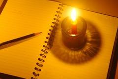 Lápiz puesto en el cuaderno con la luz de la vela Imagen de archivo