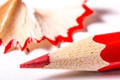 Lápiz rojo con las virutas en una textura blanca del fondo foto de archivo libre de regalías
