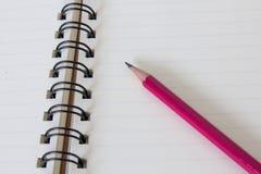 Lápiz rojo en la página del cuaderno Fotografía de archivo