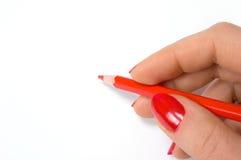 Lápiz rojo en mano de la mujer Imagen de archivo libre de regalías