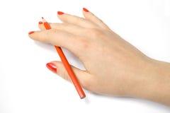 Lápiz rojo en mano de la mujer Imágenes de archivo libres de regalías