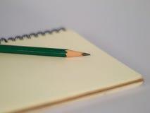 Lápiz verde en un cuaderno Fotografía de archivo