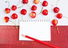 Lápiz y cerezas en blanco de la libreta Imagenes de archivo