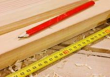 Lápiz y cinta de la medida en de madera foto de archivo