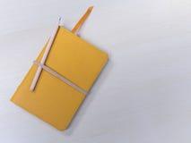 Lápiz y cuaderno en la tabla Foto de archivo