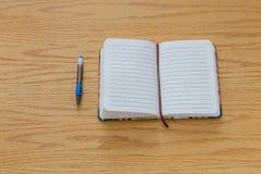 Lápiz y cuaderno en una tabla Imagen de archivo
