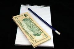 Lápiz y dinero de la libreta imagen de archivo
