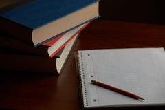 Lápiz y documento sobre el escritorio con los libros Imagen de archivo