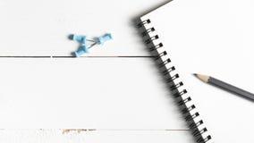 Lápiz y libreta con el perno del empuje Imagen de archivo