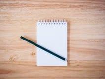 Lápiz y libreta en el escritorio de madera Foto de archivo libre de regalías