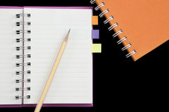 Lápiz y post-it puestos en el mini cuaderno Foto de archivo libre de regalías