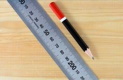 lápiz y regla inoxidable en la tabla de madera Imagen de archivo