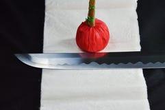 Lâmina da espada de Katana Japanese e compressa vermelha no pano branco do líquido de limpeza Fotografia de Stock