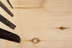 Lâminas de diversas serras que se encontram em uma folha da madeira compensada Imagem de Stock Royalty Free