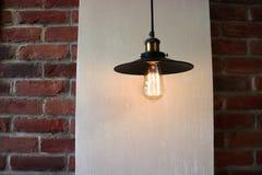 A lâmpada é suspensão preta no fundo da parede com elementos da alvenaria como o fundo fotos de stock