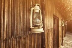Lâmpada antiquado da lanterna do óleo do querosene do vintage com a parede de madeira envelhecida Fotografia de Stock