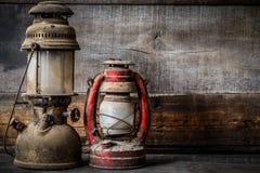 Lâmpada antiquado da lanterna do óleo do querosene do vintage que queima-se com uma luz macia do fulgor com o assoalho de madeira Fotografia de Stock