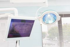 Lâmpada cirúrgica na sala de operações dental, monitor com raio X da maxila fotografia de stock royalty free