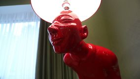 A lâmpada de assoalho sob a forma do homem vermelho video estoque